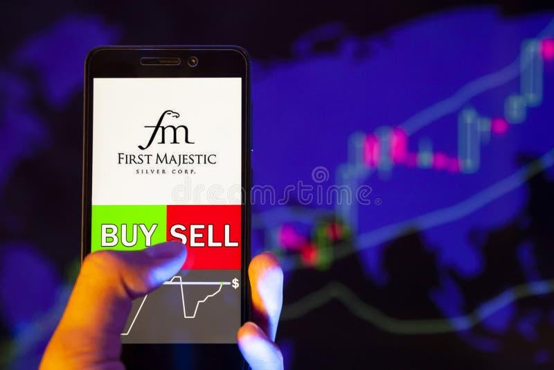 Логотип компании First Majestic Silver Corp AG на экране смартфона, рука торговца держащим мобильный телефон, показывающий покупк стоковое фото