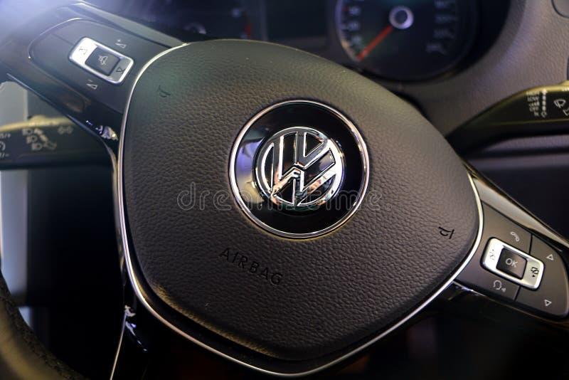 Логотип популярного немецкого VW Фольксваген производителя автомобилей на руле стоковые изображения rf