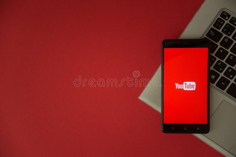 Логотип Youtube на экране smartphone помещенном на клавиатуре компьтер-книжки стоковые фотографии rf