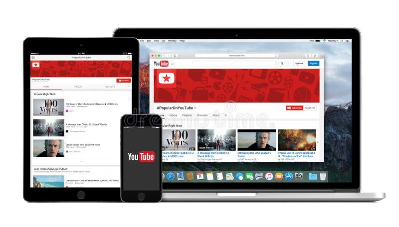 Логотип YouTube app на iPad iPhone и экране Macbook Pro стоковое фото rf