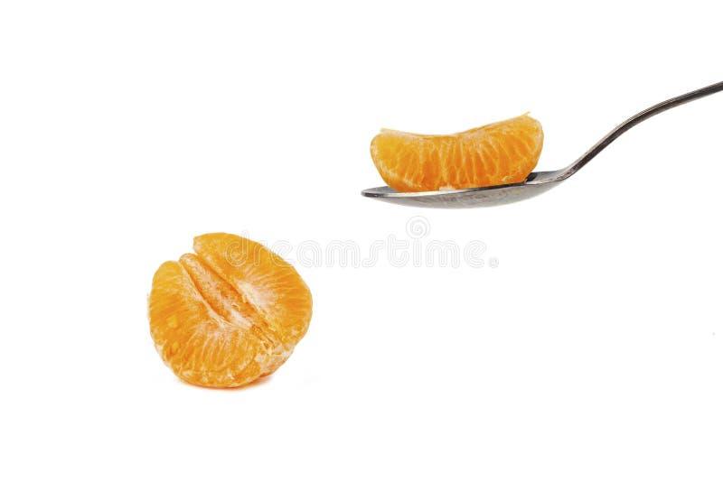 Ложка держит кусок мандарина на белой предпосылке стоковое фото