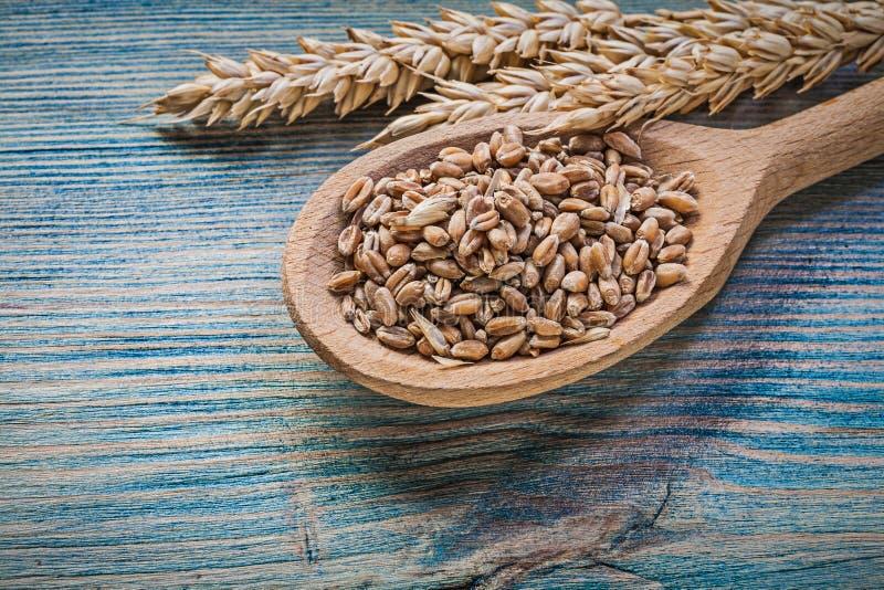 Ложка золотых зерен ушей рож пшеницы деревянная на винтажной деревянной доске стоковые фото