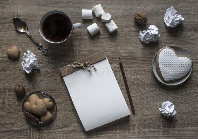 Ложка мяты бумаги шишки гайки зефира кофе кружки коричневого цвета карандаша сердца печенья плиты деревянного блокнота ремесла ло стоковые изображения