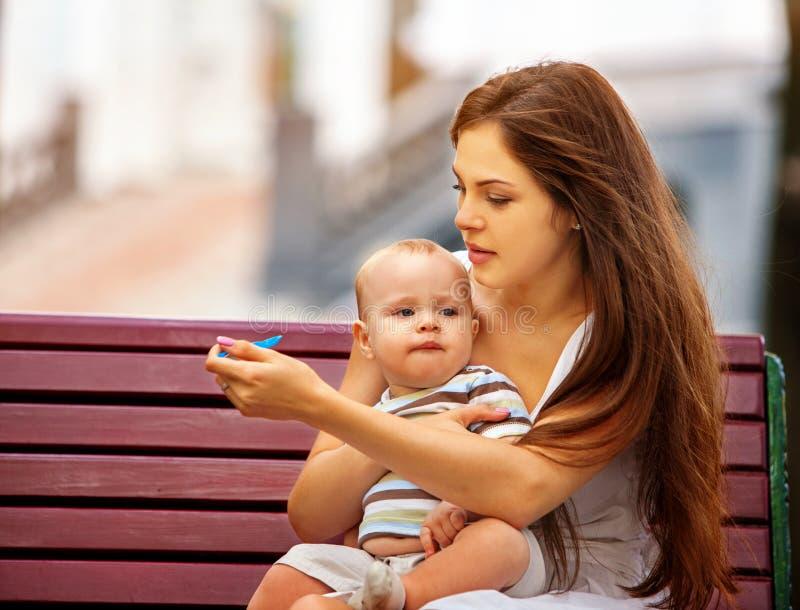 Ложка младенца подавая матерью в парке внешнем Тон цвета стоковое изображение