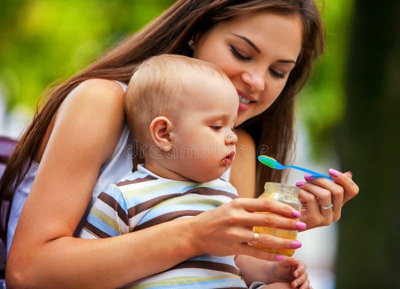 Ложка младенца подавая матерью в парке внешнем weaning стоковая фотография
