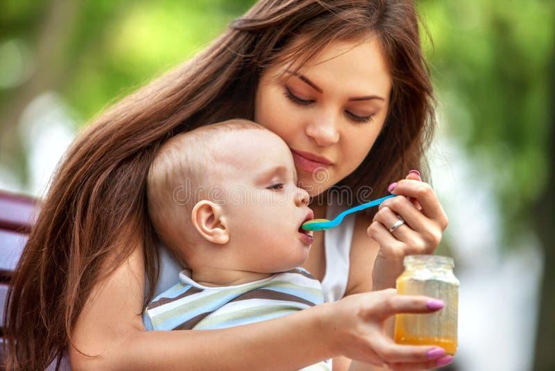 Ложка младенца подавая матерью в парке внешнем weaning стоковые изображения rf