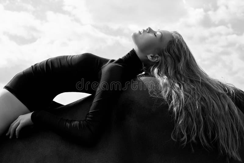 Лож всадника девушки согнутые на лошади в поле Портрет моды женщины и конематки лошади в деревне в небе стоковая фотография rf