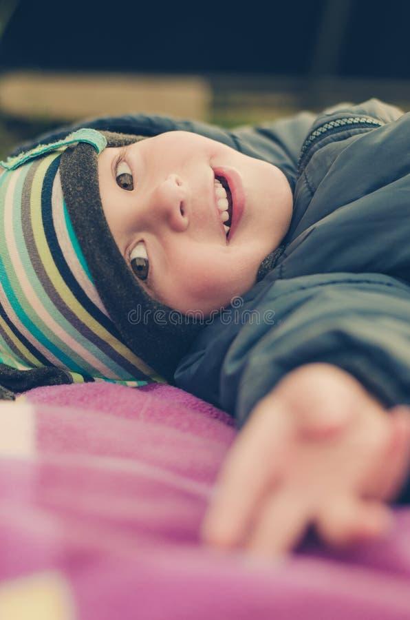 Лож и улыбки мальчика ребенок счастливый стоковые фото