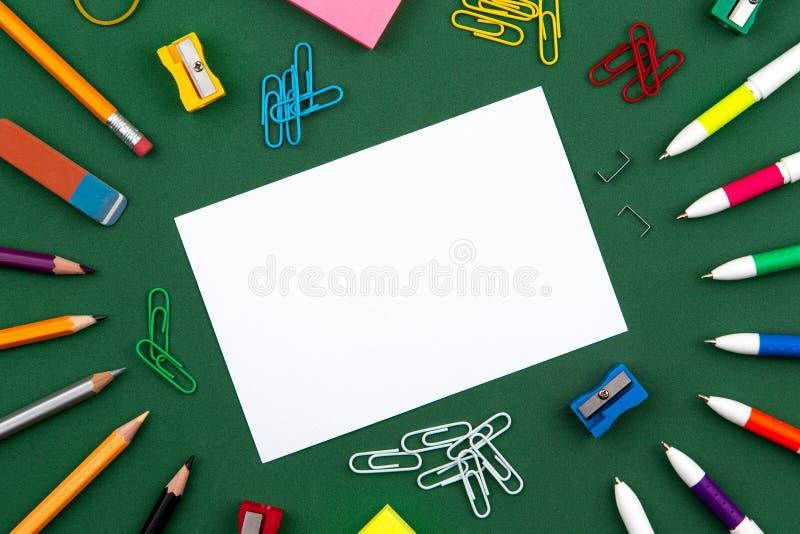 Лож канцелярских принадлежностей школы на зеленом школьном правлении формируя рамку для текста около карандаша и скомканных стран стоковая фотография rf