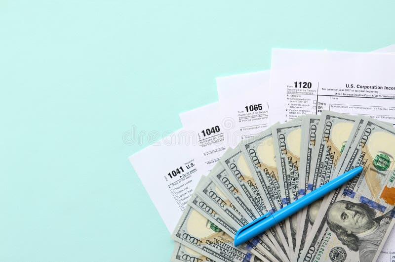 Лож налоговых форм около 100 долларовых банкнот и голубой ручки на светлом - голубая предпосылка Налоговая декларация подоходного стоковая фотография rf