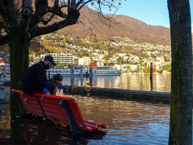 Локарно, отец и сын играя ход листья в воде стоковое изображение