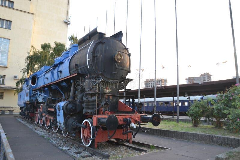 Локомотив пара перед старым железнодорожным вокзалом стоковое фото rf