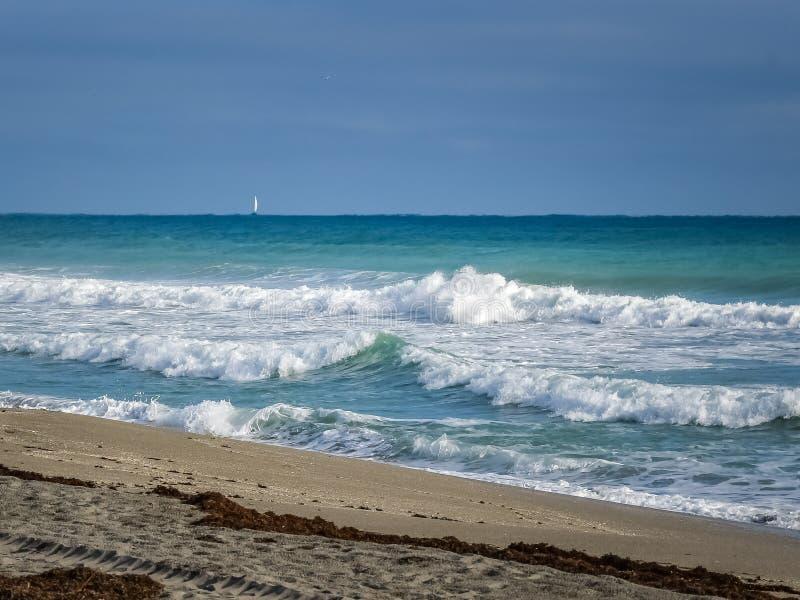 Ломая волны и парусник стоковые изображения