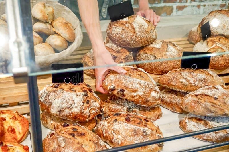 Ломти хлеба на счетчике пекарни будучи проданным и скомплектованном хлебопеком, за форточкой стекла Европейский магазин хлеба рем стоковые фотографии rf