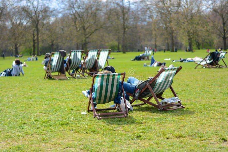 лондонец сидит на deckchairs в Гайд-парке Лондон, Англия стоковое фото