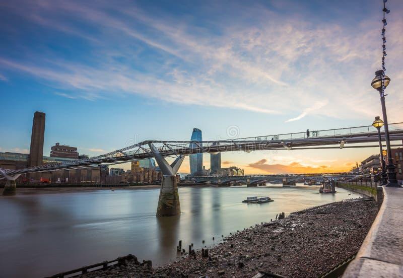 Лондон, Англия - красивый заход солнца на мосте тысячелетия с рекой Темзой и небоскребы стоковая фотография