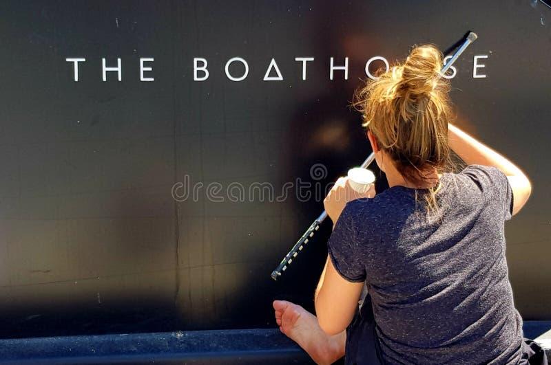 Лондон, Англия - 25-ое июня 2018 - молодое знак-сочинительство женщины имя на сторону шлюпки канала, в тазе Paddington  стоковое фото