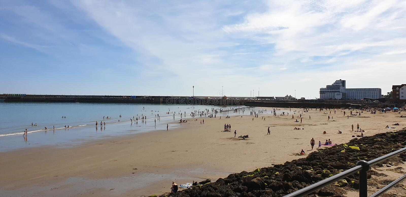 Лондон, Англия, Folkestone, Кент: 1-ое июня 2019: Туристы на солнечных песках приставают наслаждаться к берегу красивой солнечнос стоковое фото