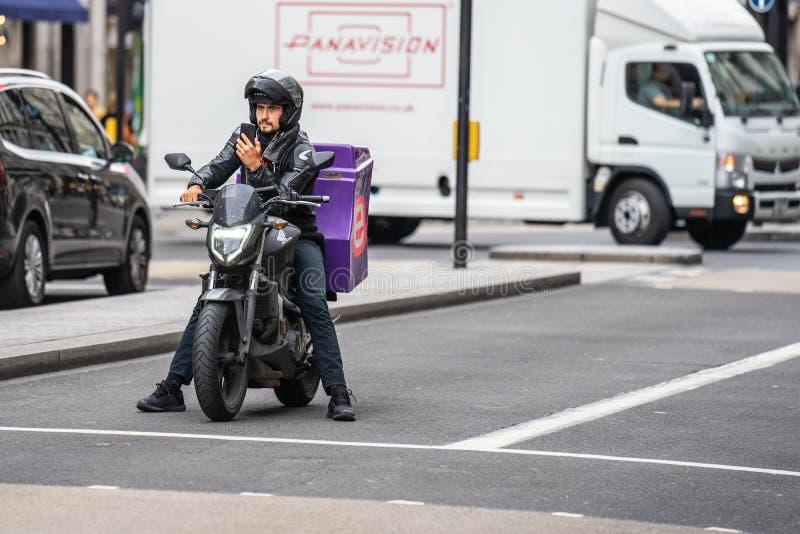 Лондон, Великобритания, 28-ое июля 2019 Работник доставляющий покупки на дом пиццы на мотоцикле в улице используя умный телефон стоковая фотография