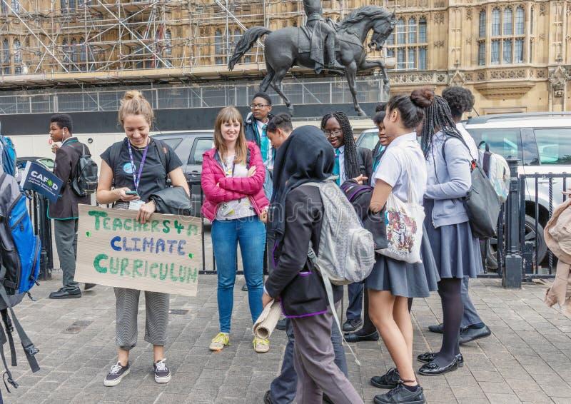 Лондон/Великобритания - 26-ое июня 2019 - учитель и группа в составе студенты держа знак об изменении климата стоковое изображение