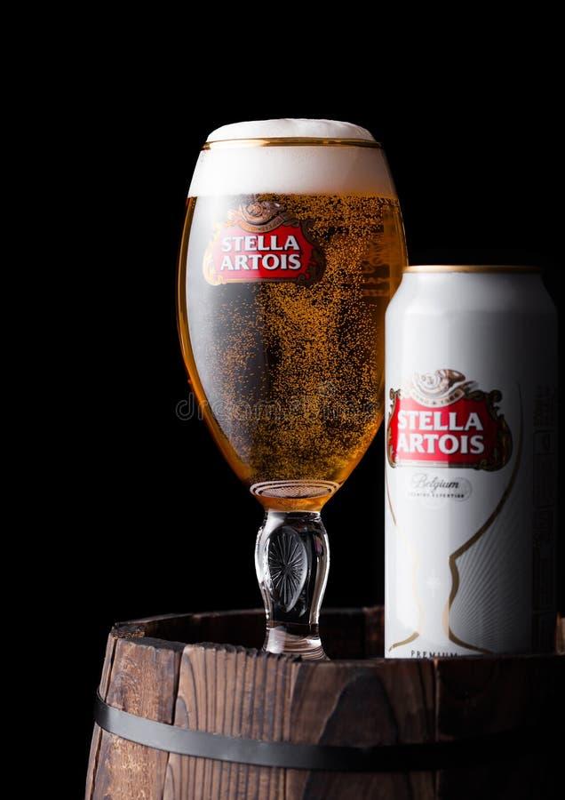 ЛОНДОН, ВЕЛИКОБРИТАНИЯ - 6-ОЕ ИЮНЯ 2018: Холодное стекло и алюминиевая чонсервная банка пива Стеллы Artois на старом деревянном б стоковое изображение rf