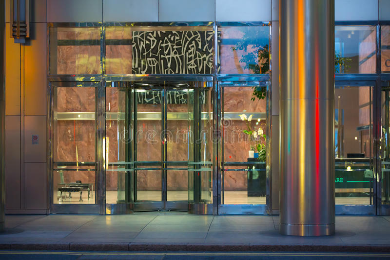 ЛОНДОН, ВЕЛИКОБРИТАНИЯ - 7-ОЕ СЕНТЯБРЯ 2015: Вход офисного здания в свет ночи Канереечная ночная жизнь причала стоковое изображение rf