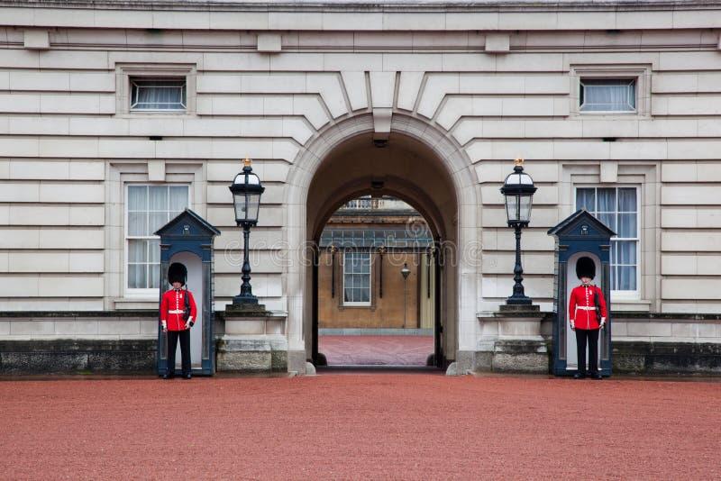 ЛОНДОН - 17-ОЕ МАЯ: Великобританские королевские предохранители защищают вход к Букингемскому дворцу 17-ого мая 2013 стоковые фото