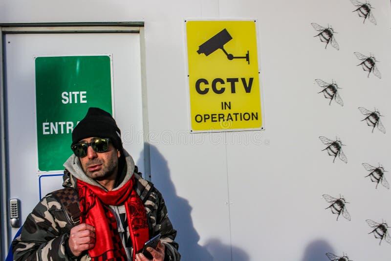 ЛОНДОН - 16-ОЕ ФЕВРАЛЯ 2018: Неопознанный человек с красными шарфом и солнечными очками рядом со стеной знака наблюдения камеры C стоковые фотографии rf