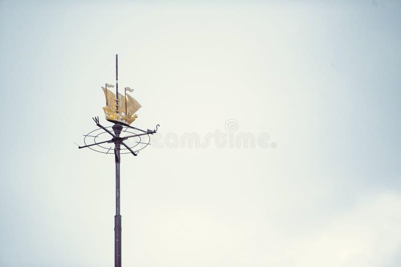 Лопасть погоды с силуэтом парусника и направления компаса стоковое изображение