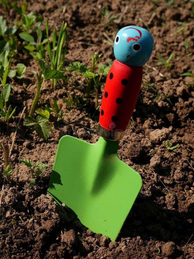 Лопаткоулавливатель игрушки при зеленая ручка лезвия и ladybug jabbed в почве сада стоковая фотография rf