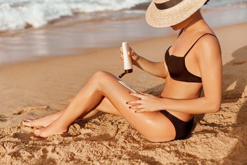 Лосьон Suntan Сексуальная молодая женщина прикладывая сливк солнцезащитного крема солнечную на пляже r Сливк Солнца стоковая фотография