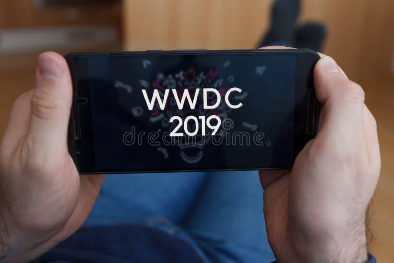 ЛОС-АНДЖЕЛЕС, КАЛИФОРНИЯ - 3-ЬЕ ИЮНЯ 2019: Конец до мужских рук держа смартфон наблюдая WWDC 2019 Иллюстративная передовица стоковое изображение