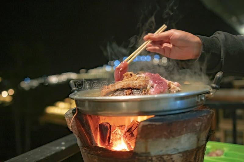 лоток для тайского барбекю или животики Moo Kra поверх тайской традиционной плиты с рукой женщины стоковые изображения rf