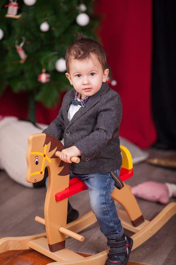 Лошадь малой езды мальчика деревянная тряся перед рождественской елкой стоковое фото