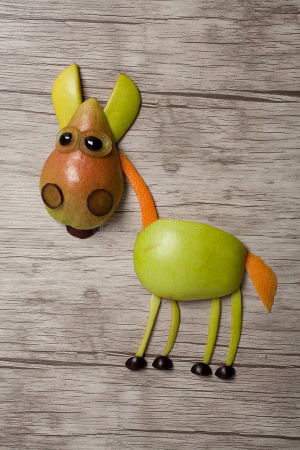 Лошадь сделанная с яблоком и грушей на деревянной предпосылке стоковые изображения rf