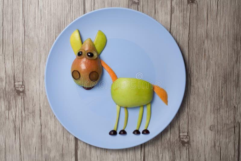 Лошадь сделанная с яблоком и грушей на плите и деревянной текстуре стоковые фото