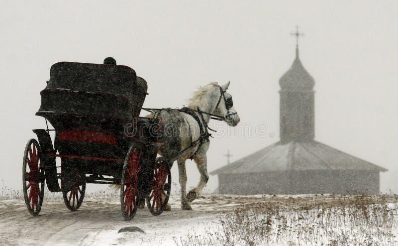 Лошадь с экипажом двигает вдоль дороги зимы на предпосылке старого здания стоковая фотография rf