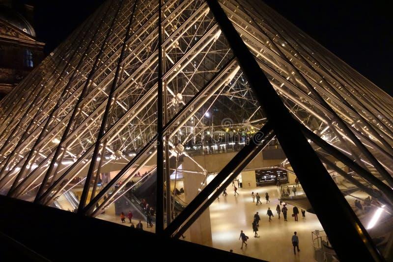 Лувр Пирамида в ночь с посетителями стоковое изображение