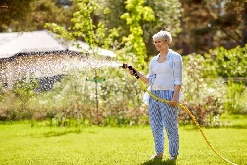 Лужайка старшей женщины моча шлангом на саде стоковое изображение