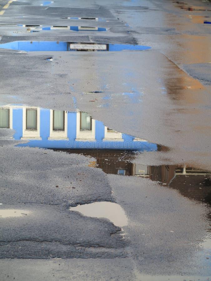 Лужицы с голубым отражением дома стоковое фото