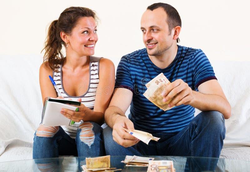 Лукавая жена прося усмехаясь деньги человека ходить по магазинам стоковое изображение rf