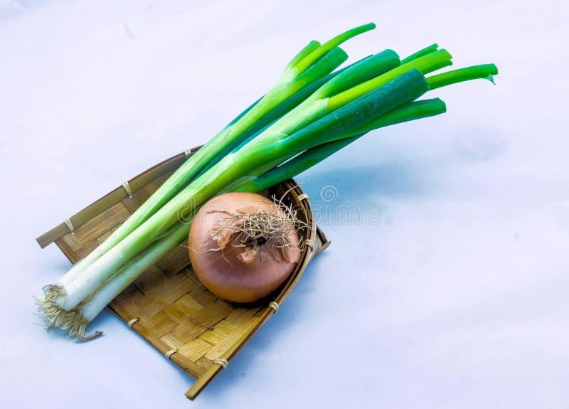 Лук-порей и лук на заплетенной деревянной плите стоковая фотография rf