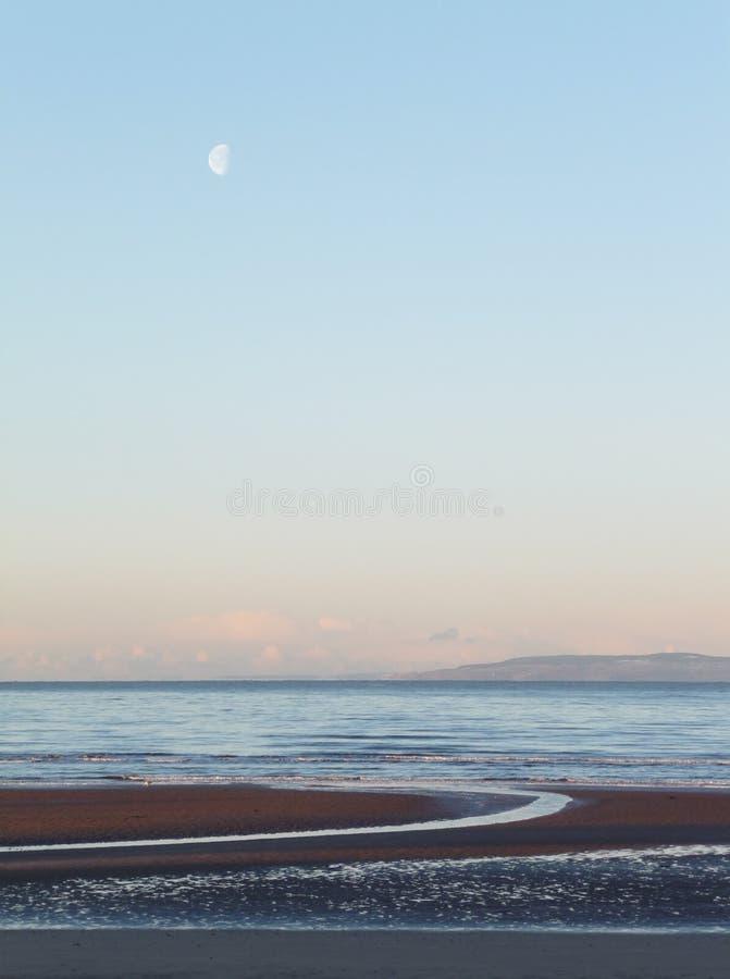 Луна над лиманом Клайда, от пляжа Prestwick, Шотландия стоковая фотография