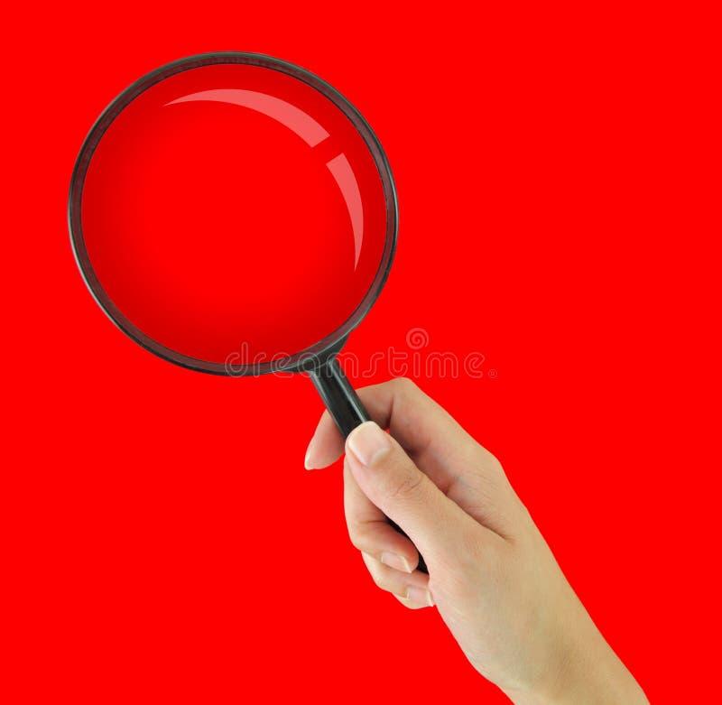 Лупа на красной предпосылке стоковое фото