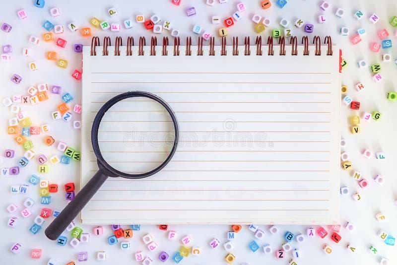 Лупа на пустой тетради с письмом алфавита отбортовывает ба стоковые изображения