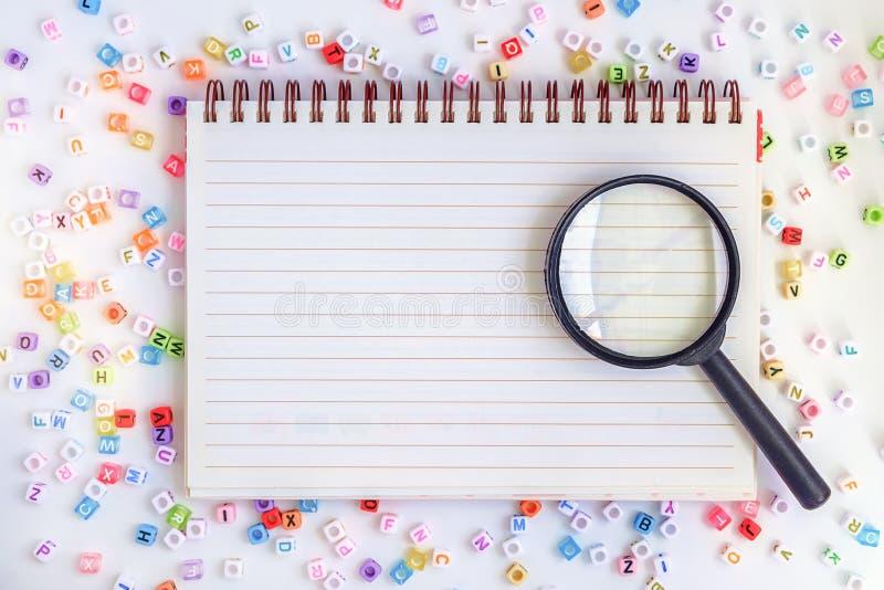 Лупа на пустой тетради с письмом алфавита отбортовывает ба стоковое изображение