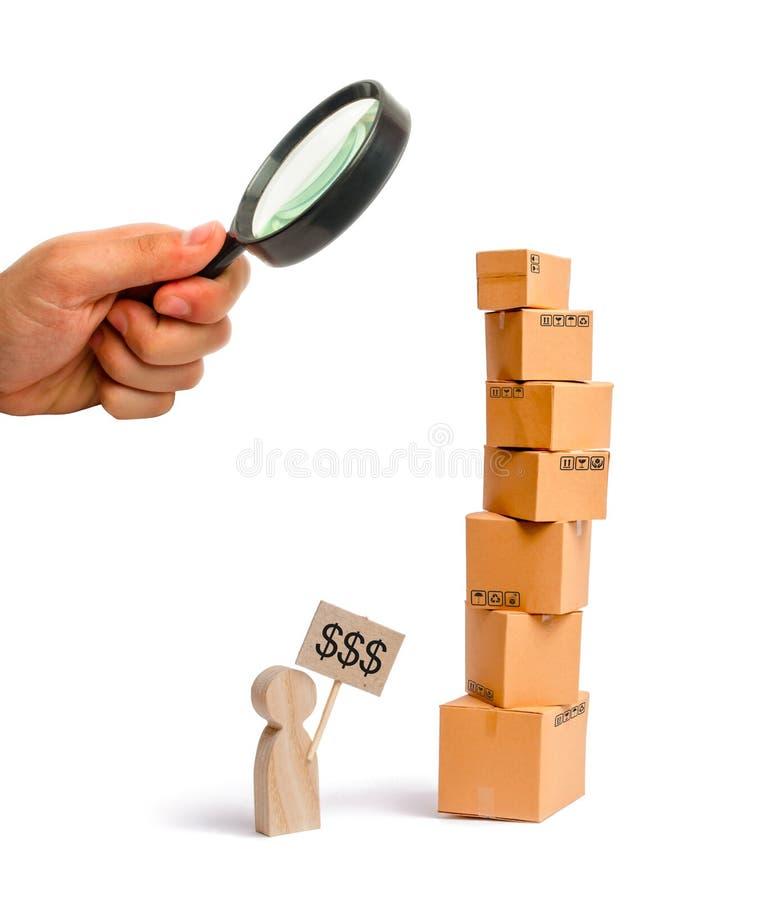 Лупа смотрит башню картонных коробок и диаграмму человека со знаком внутри его руки Человек продает его товары стоковые фото