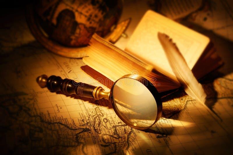 Лупа с картой книги, ручки и мира на старой карте стоковая фотография