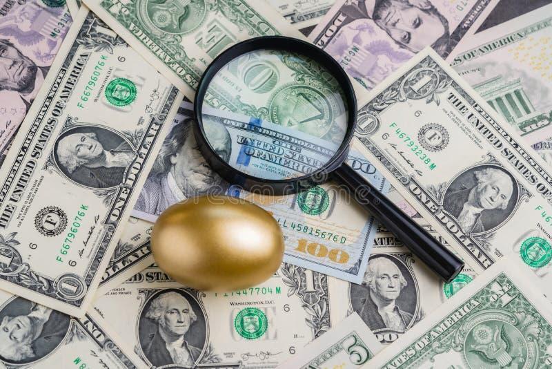 Лупа с сияющим золотым яйцом под кучей метафоры денег банкнот доллара США Америки драгоценного богатства, считая хороший стоковое изображение rf