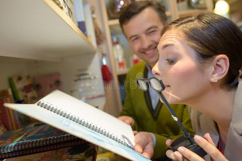 Лупы женского клиента пробуя на магазине розничной торговли стоковое изображение rf